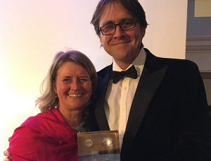 Julia Martin holding sliver award for Devon Yurt