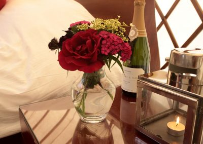 flowers candles and fizz beside yurt bed