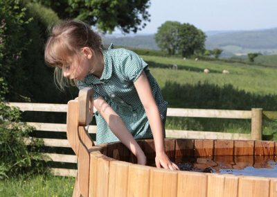 Little girl playing beside devon yurt hot tub