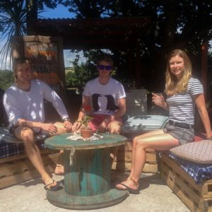 2 boys and a girl sitting in the sun at a pub table